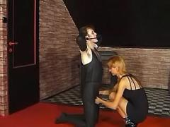 Dominatrix ties slave hand and foot